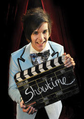 Boy in powder blue tuxedo holding showtime clapperboard