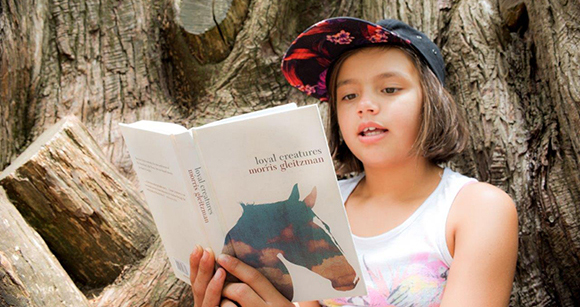 Image of girl in tree reading a book