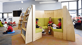 Children sit reading in a reading nook