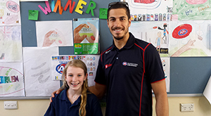 Collingwood footballer Patrick Karnezis with with Montmorency South Primary student Tyalla Kellam.