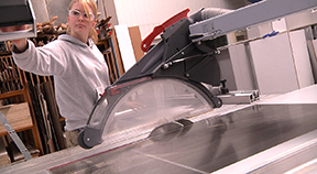An apprentice operates a table saw.