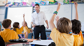 Students with their hands up in the classroom.
