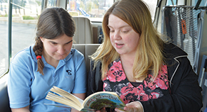 Bethany Mugford reads a book with a student.