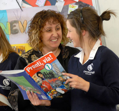 Girl student and teacher discussing an Italian language book