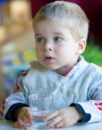 very young boy with a glass of water