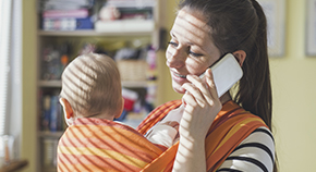Mother on phone with baby strapped to chest