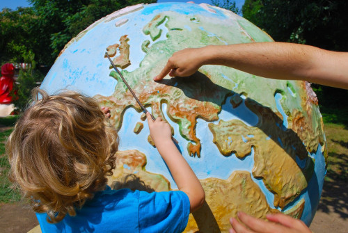 child pointing at a world globe