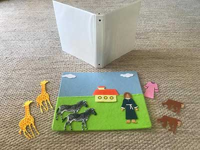 image shows equiptment: folder, felt square with sky, grass, a house, horses, giraffes, monkeys and a lady.