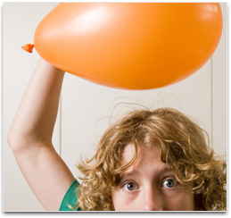 Student holding balloon above head so hair is standing up & attracted to it