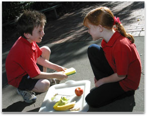 Two young students are in conversation over a tray of fruit.