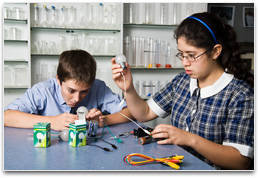 Two students with several batteries, light globe & connecting wires.