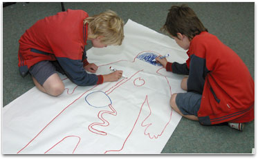 2 students are drawing onto an outline of a body on a large piece of paper.
