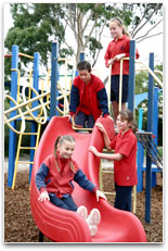 Students on play equipment, watching a girl slide down a playground slide.