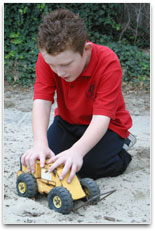 A young student in a sand pit pushing a model grader along to form a road.