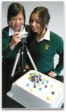2 students are taking stop frame images of marble sized plasticine balls.