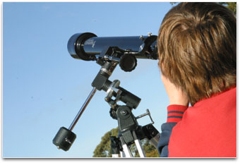 A student is looking through a telescope at the daytime sky.