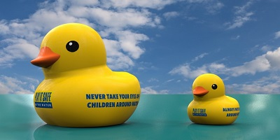 A computer-generated image of two rubber ducks floating on water, with the Water Safety Week logo and slogan on the side
