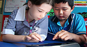 Young girl and Asian boy using iPad together