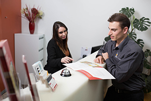 A man and a woman inspect a brochure